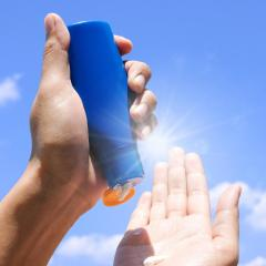 Hand of female holding sunscreen bottle up to the sun